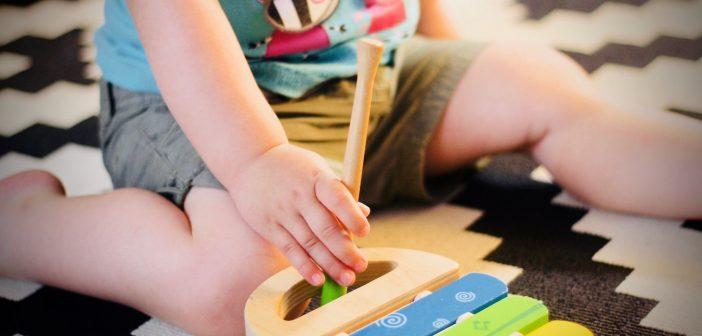 Enfant qui joue avec un xylophone en bois